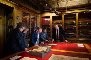 Group of people examining documents in the archive