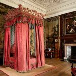 Four poster bed with red damask curtains