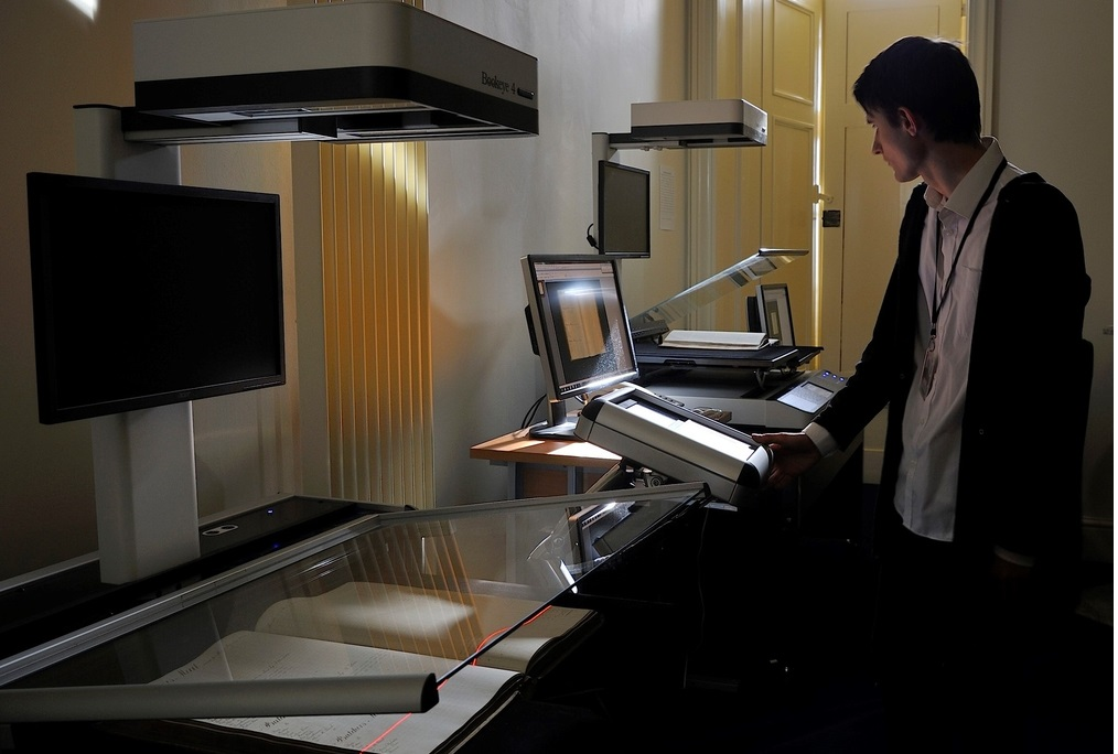 Staff member scanning documents on a hi-tech scanning machine