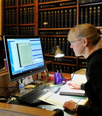 Woman sitting at computer reviewing manuscripts on a computer screen