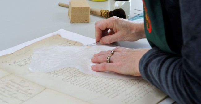 Closeup of hands working on preservation of a manuscript