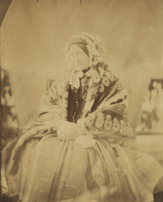 Three quarters length albumen print of Mary, seated and wearing a shawl and headress